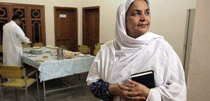 Maryam Bibi, a Pakistani woman, wearing a white shawl and holding a book.