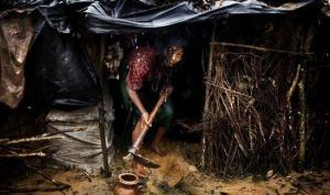 A Rohingya woman collects rain water.