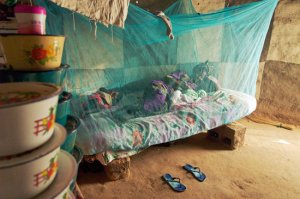 An African woman lies under a light-blue bed net.