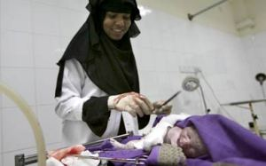 Woman a black hijab cleans a newborn baby.
