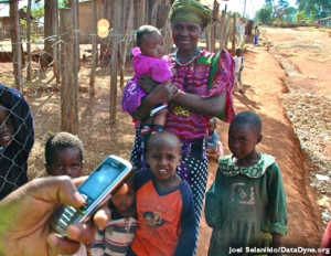 A man holds a cell phone in front of a woman with four children.