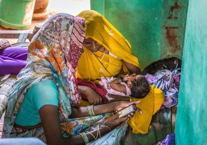 An accredited social health activist (ASHA) counsels a new mother using the mSakhi video on breastfeeding in Badagaon block, Jhansi district, Uttar Pradesh, India.