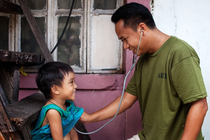 An Army nurse examines a young boy as part of his community service in San Andres Bukid, Manila, Philippines.